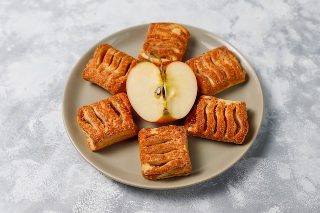 Puff pastry cookies filled with apple jam and fresh red apples on light concrete