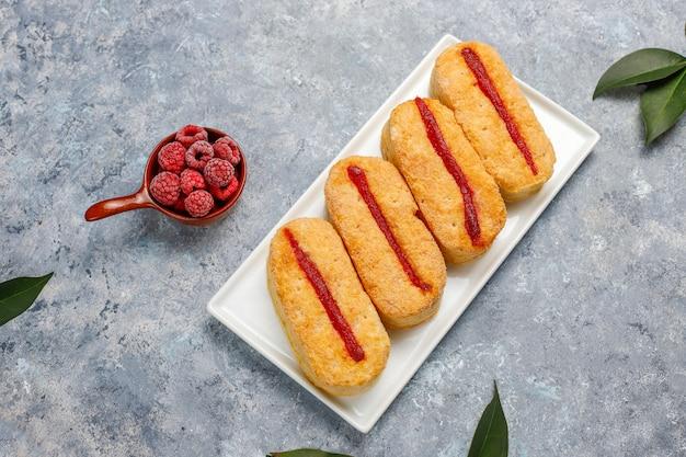 Biscotti di pasta sfoglia con marmellata di lamponi e lamponi congelati su luce