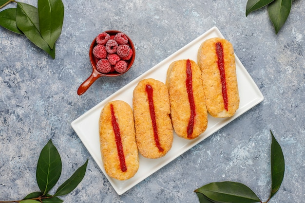 Puff pastry cookies with raspberry jam and frozen raspberries on light