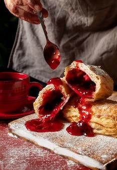Puff pastry dessert red jam hand viburnum cherry cup coffee black background