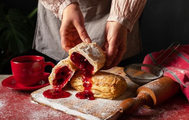 パイ生地デザート赤ジャム手ガマズミチェリーカップコーヒー黒背景
