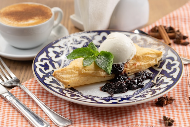 Puff pastry dessert with berry jam and a ball of vanilla ice cream decorated with a mint leaf in a plate with a traditional uzbek