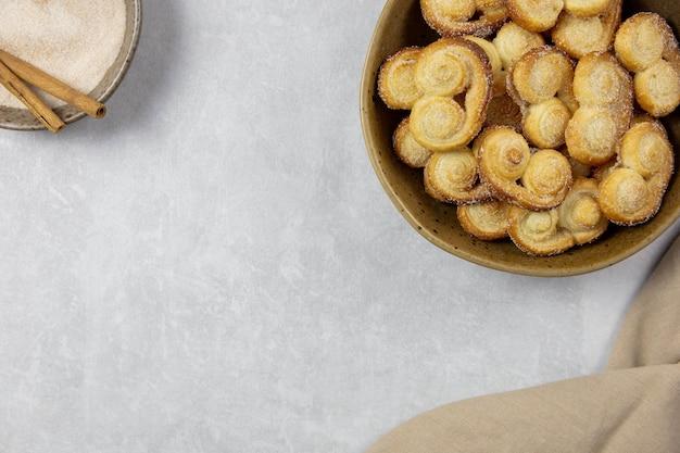 Ушко из слоеного теста, печенье palmier в миске с корицей и сахаром на светлом бетонном фоне с копией пространства.