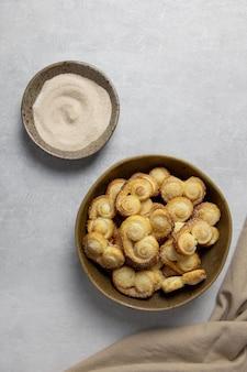 퍼프 페이스 트리 작은 구멍, 계피와 밝은 콘크리트 배경에 설탕 그릇에 팔미에 쿠키.