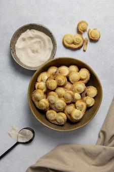 Ушко из слоеного теста, печенье palmier в миске с корицей и сахаром на светлом бетонном фоне.