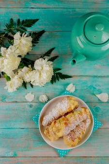 クリームと木製のテーブルにティーポットとパイ生地の角
