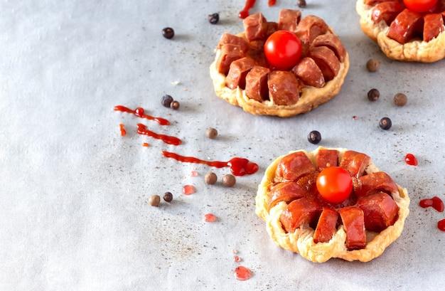 Мини-пирог из слоеного теста с колбасой и помидорами черри фон запеченной бумаги выборочный фокус