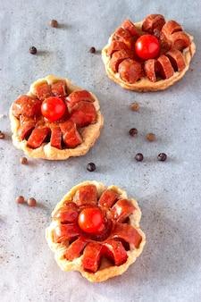 Мини-пирог из слоеного теста с колбасой и помидорами черри. запеченный бумажный фон.