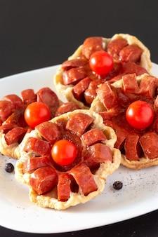 Мини-пирог из слоеного теста с колбасой и помидорами черри на тарелке. темный деревянный фон.