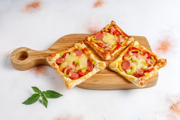 Мини-пиццы из слоеного теста с сосисками.