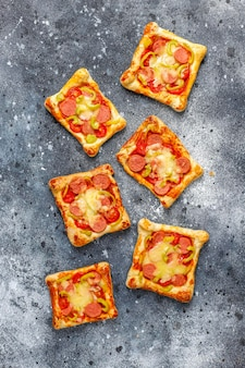 Puff pastry mini pizzas with sausages.