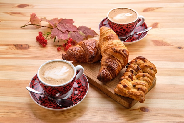 Puff pastry raisin bun and crispy croissant on wooden table with coffee