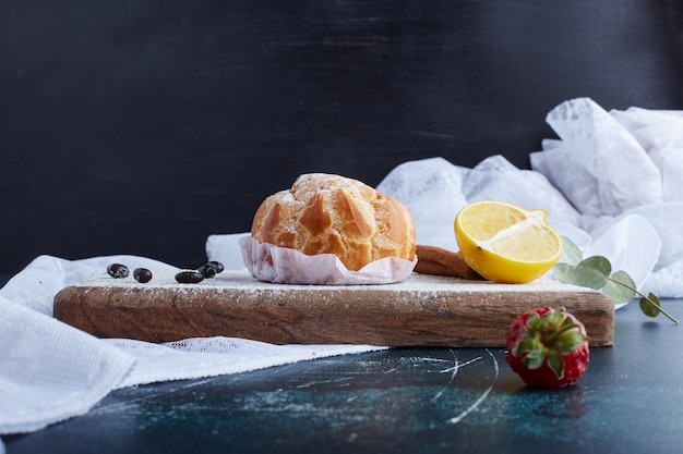 Puff pastry with a lemon on wooden board.