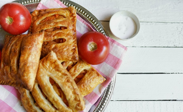 Puff pastry with tomato on a white wooden table with copy space