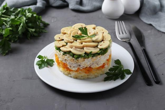 Слоеный салат с курицей, маринованными грибами, картофелем и морковью на тарелке на сером фоне. крупным планом