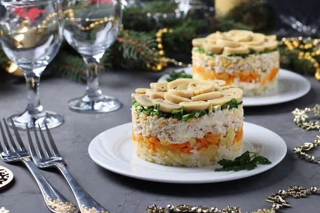 Слоеный салат с курицей, маринованными грибами, картофелем и морковью на тарелках. новогодняя композиция