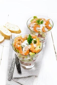 エビ、アボカド、新鮮なキュウリ、ピーマン、トマトのパフサラダ、明るい木の板の背景にタオル、パン、フォークの2つのガラスグラスにヨーグルトソースで味付け