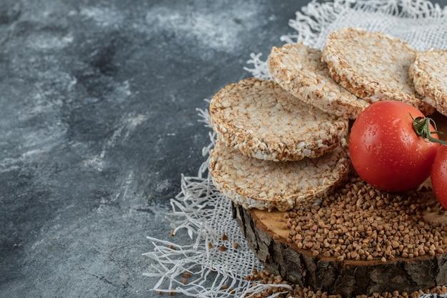 Pane croccante soffiato, pomodori e grano saraceno crudo su superficie di marmo