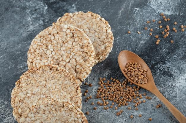 Pane croccante soffiato e cucchiaio di legno di grano saraceno crudo sulla superficie di marmo