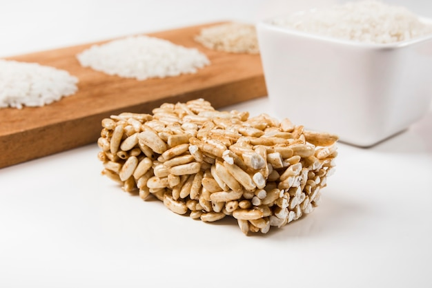 Puffed rice bar with uncooked white rice on white backdrop