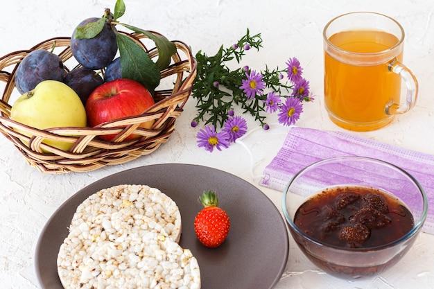 パフライスケーキ、皿にイチゴ、お茶、ジャムの入ったガラスのボウル、果物の入った籐のバスケット、白い構造の表面に医療用保護マスク