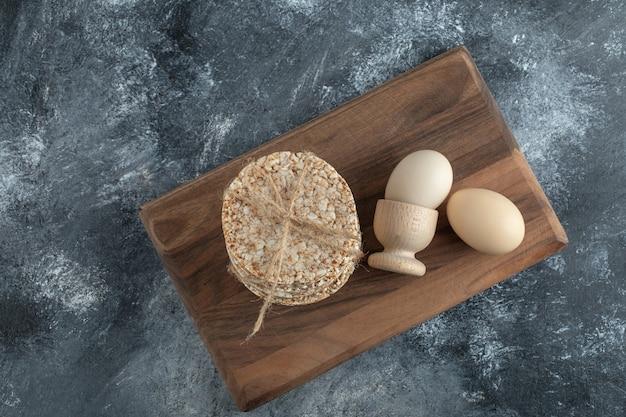 Torte di riso soffiato e uova su tavola di legno