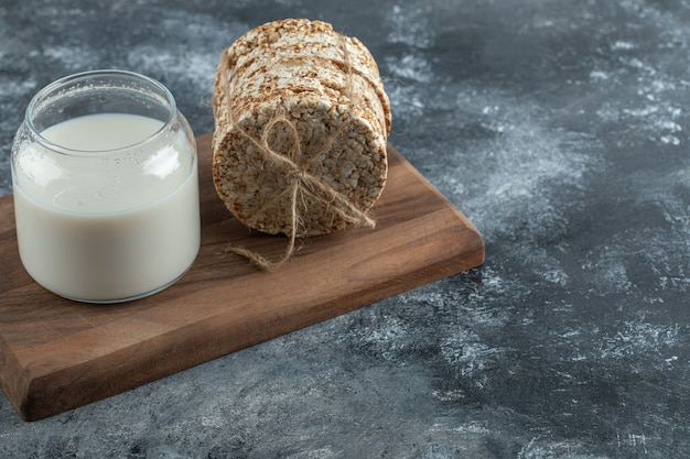 Puffed rice cakes and fresh milk on wooden board