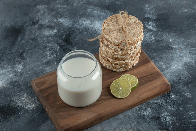 Puffed rice cakes, lemon slice and fresh milk on wooden board