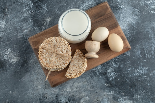 Puffed rice cakes, milk and eggs on wooden board