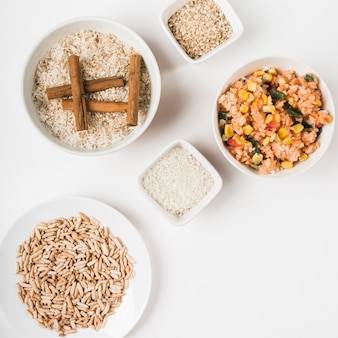 Puffed rice; chinese fried rice and uncooked rice with cinnamon sticks on white backdrop