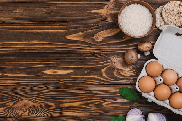 Puffed rice; rice grains; mushroom; eggs and onion over wooden desk