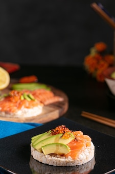 暗いテーブルの上に生鮭とアボカドをまぶしたポン菓子