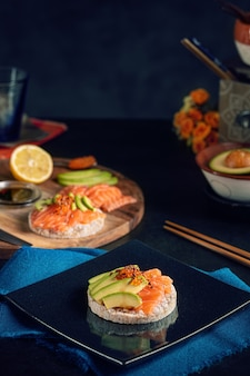 Puffed rice spread with raw salmon and avocado on a dark table