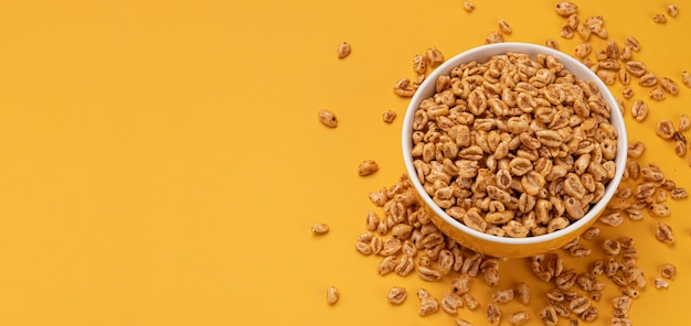 Puffed wheat cereal in bowl on yellow background, honey air rice, top view