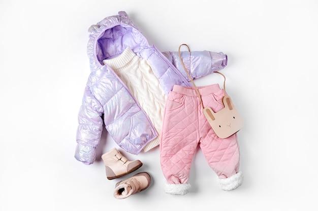 흰색 바탕에 패딩 재킷, 따뜻한 바지, 부츠. 겨울용 아기 옷 세트입니다. 패션 아동복.