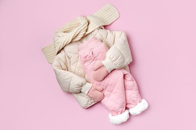 분홍색 배경에 패딩 재킷, 따뜻한 바지, 스카프. 겨울용 아기 옷 세트입니다. 패션 아동복.