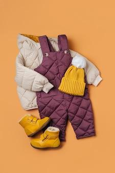 주황색 배경에 패딩 재킷, 따뜻한 바지, 모자, 부츠. 겨울용 아기 옷 세트입니다. 패션 키즈 복장.