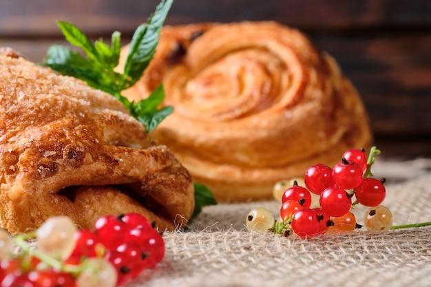 Слойки с ягодной начинкой с веточками свежей красной и белой смородины на мешковине и темном деревянном столе. крупный план.