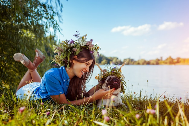 Pug dog and its master chilling by river wearing flower wreaths. happy puppy and woman enjoying summer nature outdoors