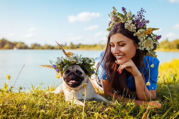 Pug dog and its master chilling by river wearing flower wreaths.
