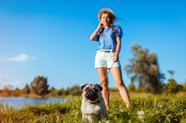 Pug dog sitting by river. happy puppy waiting a command of master. dog and woman chilling outdoors