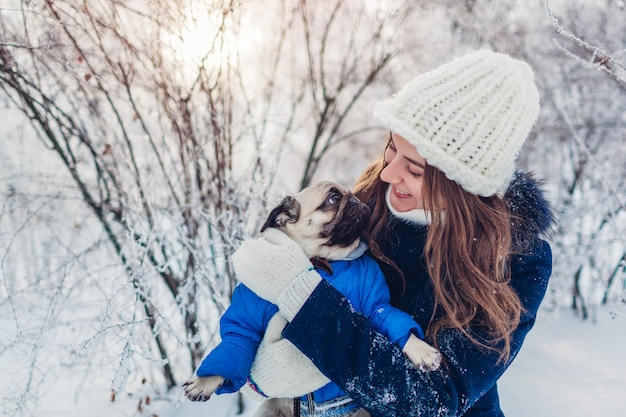 Pug dog walking outdoors. woman hugging pet in winter park. puppy wearing winter coat covered with snow.