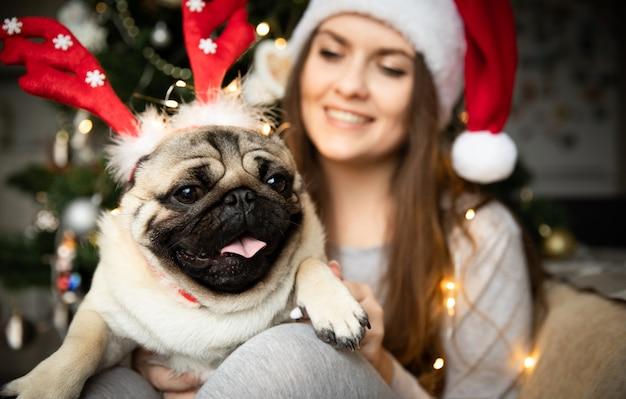 Мопс на руках у молодой женщины на рождество