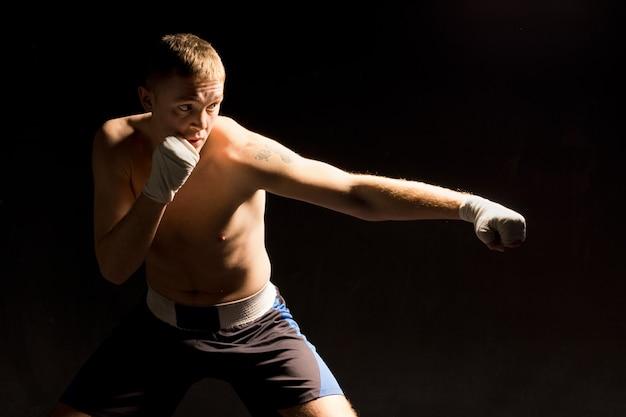펀치를 던지는 pugnacious 젊은 권투 선수
