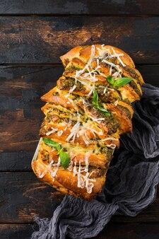 Раздвижной хлеб с итальянской пастой песто, базиликом и сыром пармезан в форме для выпечки на старом темном бетонном столе