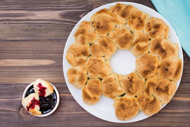 Pull apart monkey bread with black currant jam in a plate on a wooden plate. top view