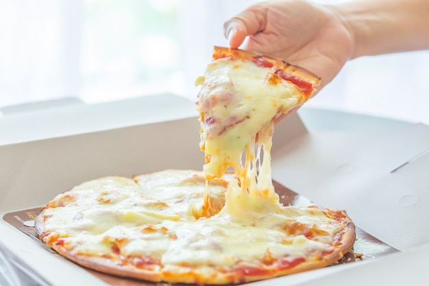 Pull pizza with hand.