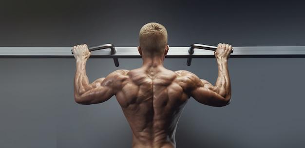 체육관에서 풀업 운동. 검은 배경에 전원 근육 보디입니다. 광배 근육을 펌핑하는 피트 니스 남자. 피트니스 및 보디 빌딩 훈련 건강 라이프 스타일 개념 가로 와이드 사진