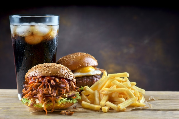 Pulled pork burger and egg cheeseburger with a glass of cola