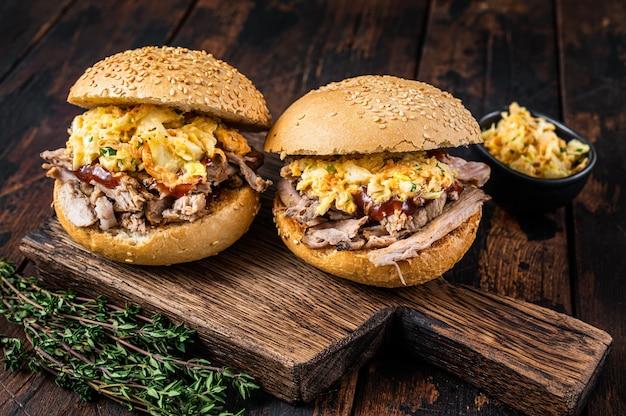 Бургер из рваной свинины с соусом барбекю и салатом из капусты. темное дерево